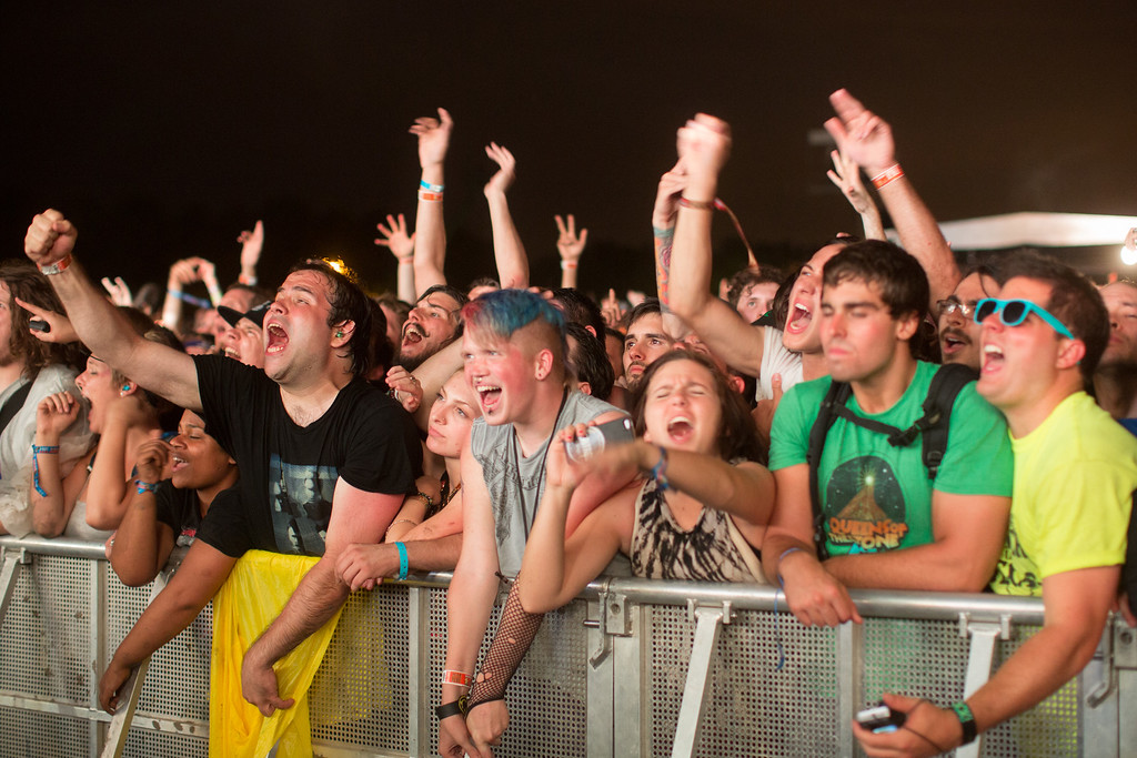 Description of . Fans cheer while the band Nine Inch Nails performs at the Lollapalooza Festival in Chicago, Friday, Aug. 2, 2013. The more than two-decade-old festival opens Friday in Chicago's lakefront Grant Park. (AP Photo/Scott Eisen)