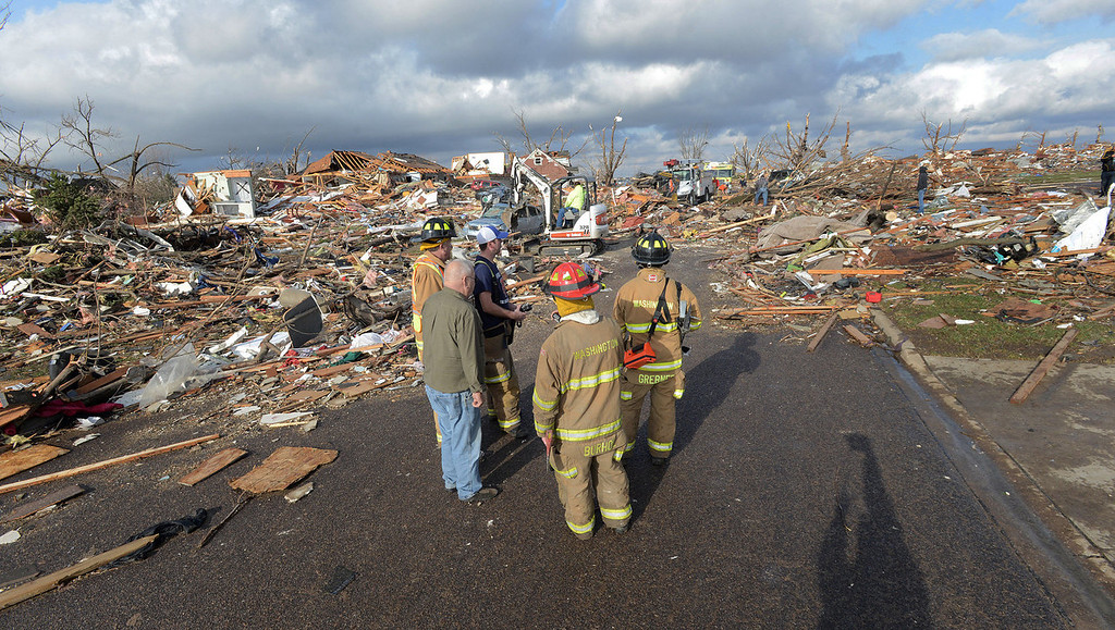 Description of . Washington, Ill., firefighters stand in the middle of Devonshire Street on the North side of Washington, Ill., after a tornado leveled at least fifty homes, Sunday, Nov. 17, 2013. High winds that followed the tornado are causing danger as homeowners and emergency workers try to search homes.  (AP Photo/The Pantagraph, Steve Smedley)