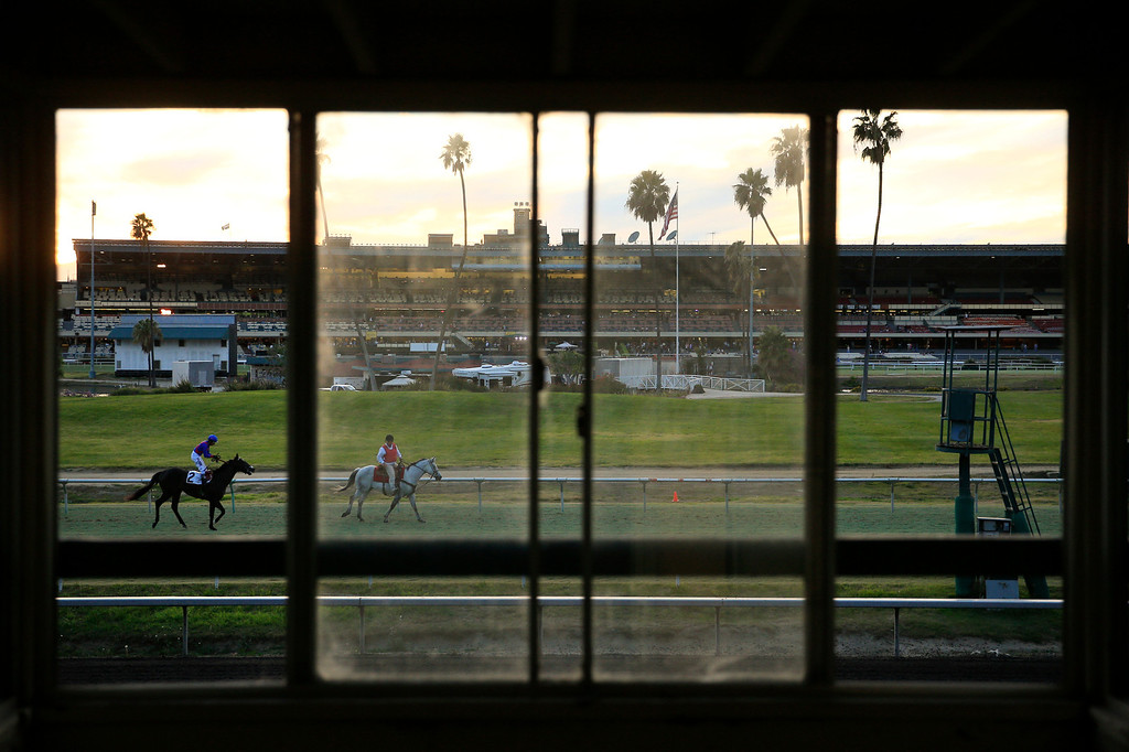 . Jockey Rafael Bejarano, left, rides Bourne Hot along the track after a race at Betfair Hollywood Park on Sunday, Dec. 15, 2013, in Inglewood, Calif. After 75 years of thoroughbred racing, Betfair Hollywood Park is closing for good. The 260-acre track that hosted Seabiscuit and the first Breeders\' Cup in 1984 will be turned into a housing and retail development starting next year. (AP Photo/Jae C. Hong)
