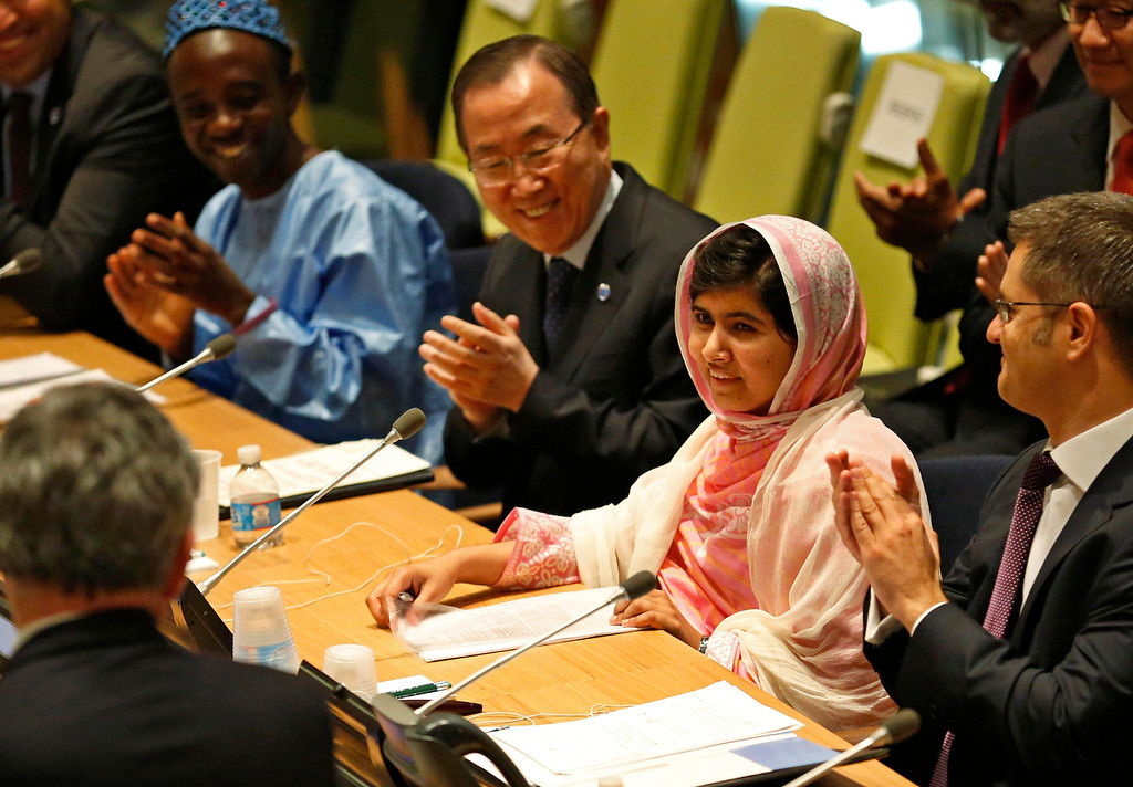 Description of . Malala Yousafzai (2nd R), is introduced before her first speech since the Taliban in Pakistan tried to kill her for advocating education for girls, at the United Nations Headquarters in New York, July 12, 2013. Wearing a pink head scarf, Yousafzai told U.N. Secretary-General Ban Ki-moon (3rd R) and nearly 1,000 students from around the world attending a Youth Assembly at U.N. headquarters in New York that education was the only way to improve lives. REUTERS/Brendan McDermid