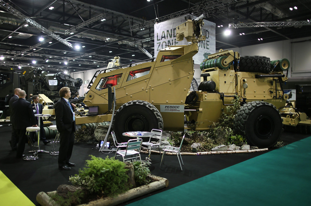 Description of . A visitor to the Defense and Security Exhibition looks at a counter mine vehicle on September 10, 2013 in London, England.  (Photo by Peter Macdiarmid/Getty Images)