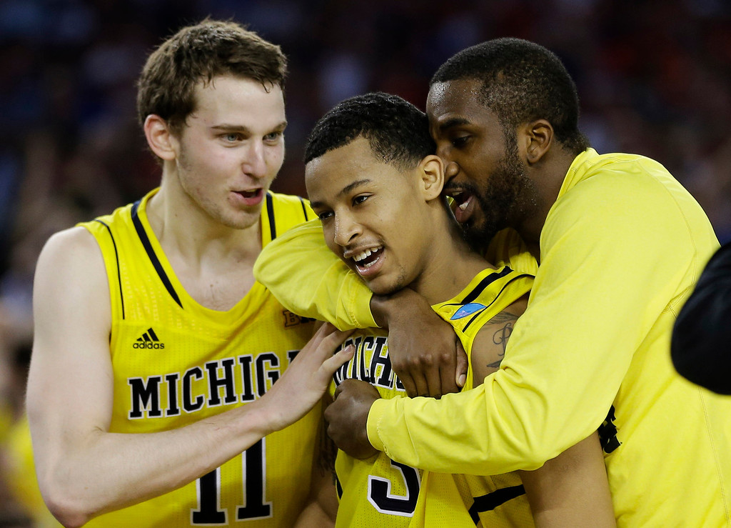 Description of . Michigan\'s Nik Stauskas (11), Trey Burke (3) and Corey Person celebrate after beating Kansas  87-85 in overtime of a regional semifinal game in the NCAA college basketball tournament, Friday, March 29, 2013, in Arlington, Texas. (AP Photo/David J. Phillip)
