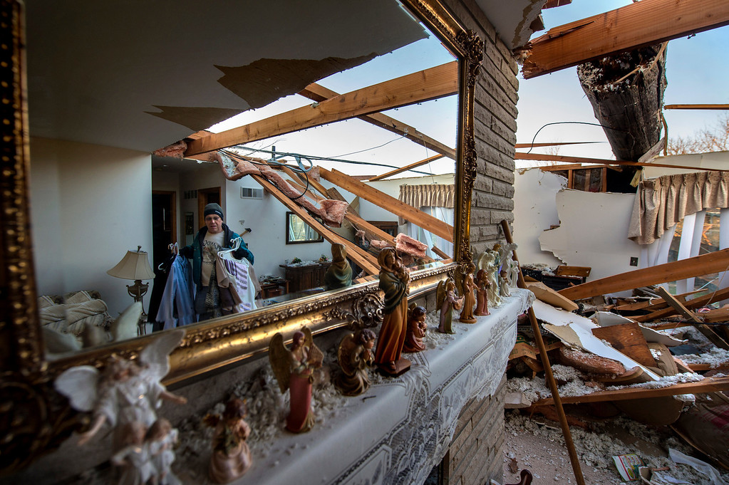 Description of . Steve Look, reflected in a mirror at left, hauls items out of Louis and Mabel Look's destroyed house in Pekin, Ill. on Monday, Nov. 18, 2013, a day after a tornado hit the area. Louis and his wife Mabel were in their kitchen when the tornado hit, tearing off the roof and flinging a utility pole in its place. Even though the roof was blown off and the chimney blocks to the fireplace collapsed inside the house, none of these Biblical figurines were disturbed by the storm. (AP Photo/Journal Star, Fred Zwicky)