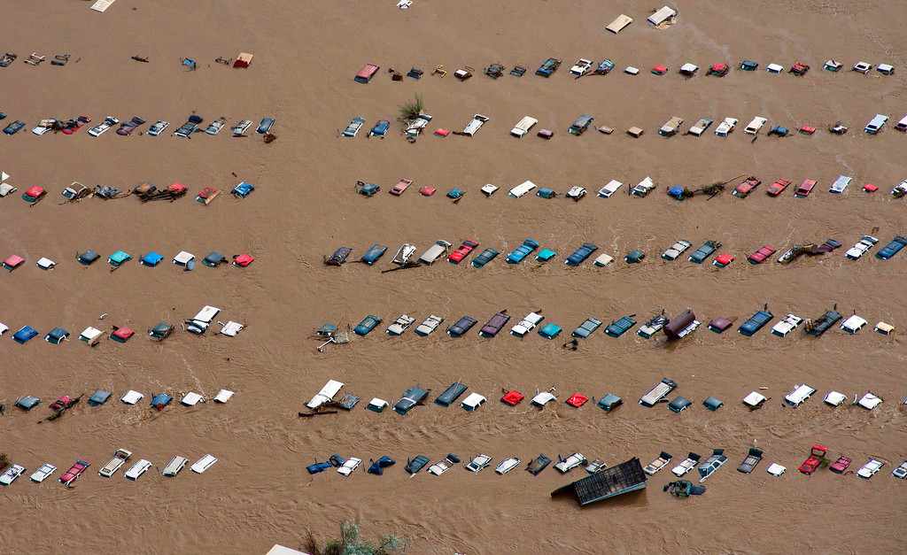 Description of . A field of parked cars and trucks sits partially submerged near Greeley, Colo., Saturday, Sept. 14, 2013, as debris-filled rivers flooded into towns and farms miles from the Rockies. Hundreds of roads, farms and businesses in the area were damaged or destroyed by the floodwaters. (AP Photo/John Wark, File)