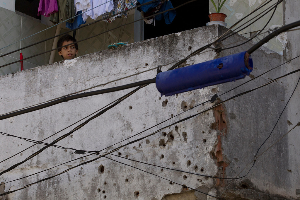 Description of . A boy watches from his home, where the wall is covered with holes from bullets of past shootings,  during an operation to occupy the Mare slum complex in Rio de Janeiro, Brazil, Saturday, April 5, 2014. More than 2,000 Brazilian Army soldiers moved into the Mare slum complex early Saturday in a bid to improve security and drive out the heavily armed drug gangs that have ruled the sprawling slum for decades. (AP Photo/Silvia Izquierdo)