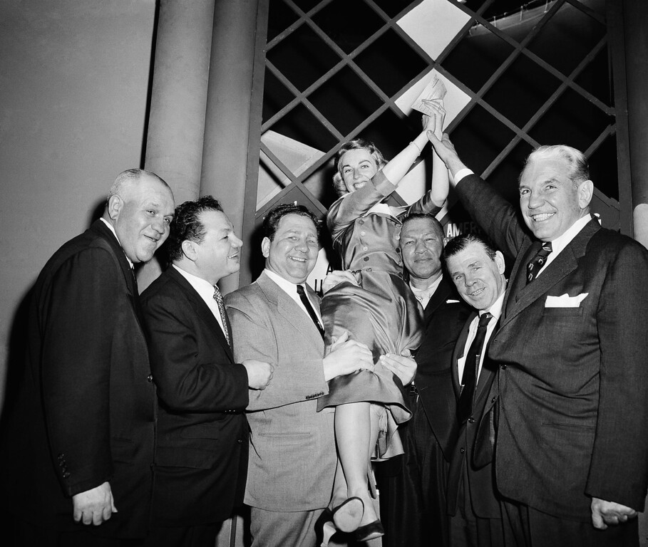 "Description of . Dr. Joyce Brothers, 28-Years old New York Psychologist, is hoisted to shoulders of some of her ""STAFF\"" of Boxers after winning top prize on the TV program, \""The $64,000 Question\"", in New York City December 6, 1955 with her knowledge of boxing. Left to right are; Marty Sommers, Tony Canzoneri, Gus Lesnevich, Dr. Brothers, Bob Olin, Mickey Walker and Eddie Eagan. (AP Photo)"