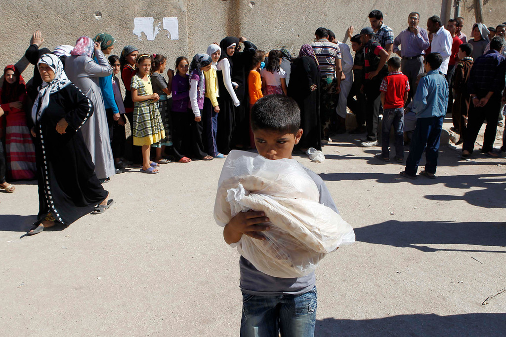 Description of . A boy carries bread bought at a local bakery to celebrate Eid al-Fitr, marking the end of the holy fasting month of Ramadan, in Azaz city, some 47 km (29 miles) north of Aleppo, August 21, 2012. REUTERS/Youssef Boudlal