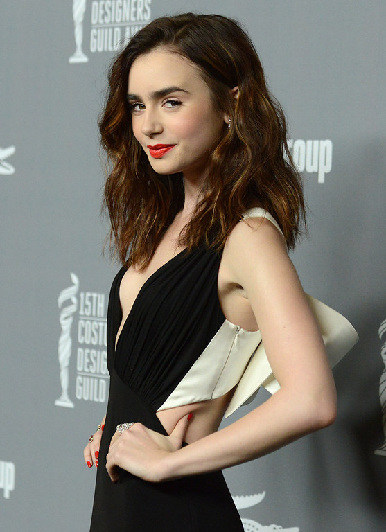 Description of . Lily Collins arrives at the 15th Annual Costume Designers Guild Awards at The Beverly Hilton Hotel on Tuesday, Feb. 19, 2013 in Beverly Hills. (Photo by Jordan Strauss/Invision/AP)
