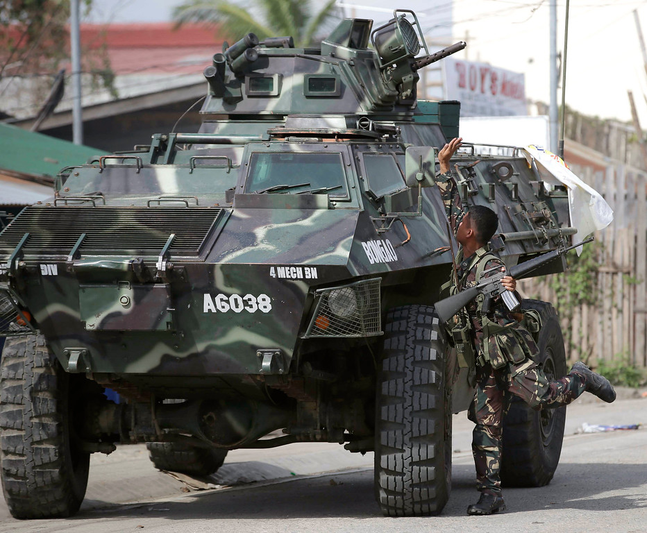 Description of . Government troopers aboard an Armored Personnel Carrier fire at Muslim rebels in an operation to rescue scores of hostages being held by the rebels, Thursday Sept. 12, 2013, in Zamboanga city in the southern Philippines.  (AP Photo/Bullit Marquez)
