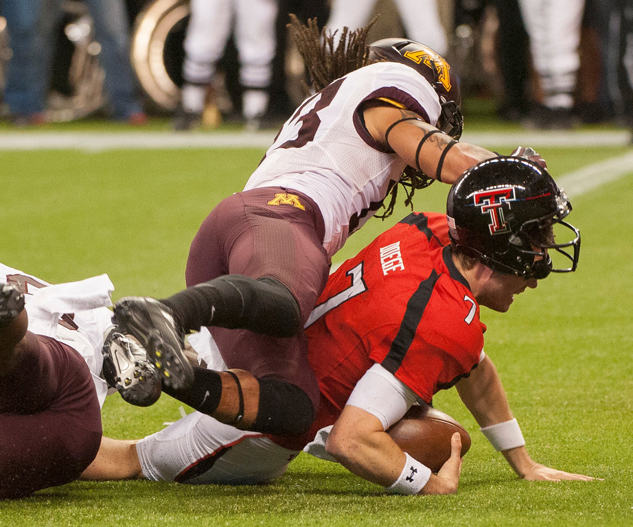 Description of . Texas Tech quarterback Seth Doege (7) dives into the end zone under Minnesota's Michael Carter for a touchdown during the second quarter of the Meineke Car Care Bowl NCAA college football game, Friday, Dec. 28, 2012, in Houston. (AP Photo/Dave Einsel)