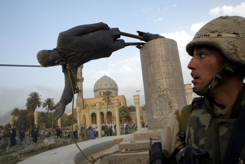 Description of . U.S. Marine Corp Assaultman Kirk Dalrymple watches as a statue of Iraq\'s President Saddam Hussein falls in central Baghdad April 9, 2003. U.S. troops pulled down a 20-foot high statue of President Saddam Hussein REUTERS/Goran Tomasevic