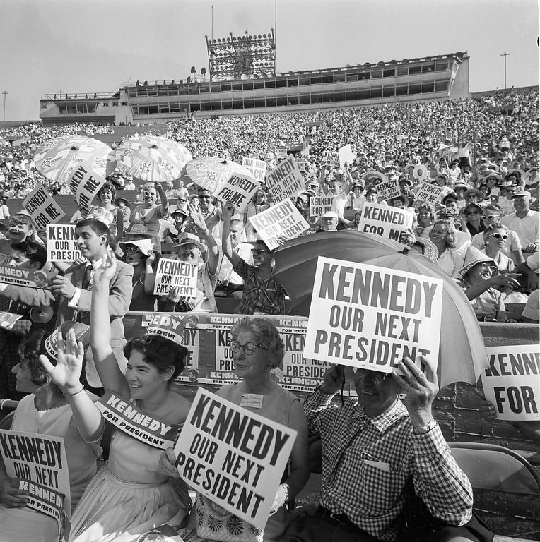 Description of . Signs of support blossom among spectators at the Los Angeles Coliseum several hours before the Democrats' presidential candidate was scheduled to give his speech accepting the nomination, July 15, 1960.  Associated Press file