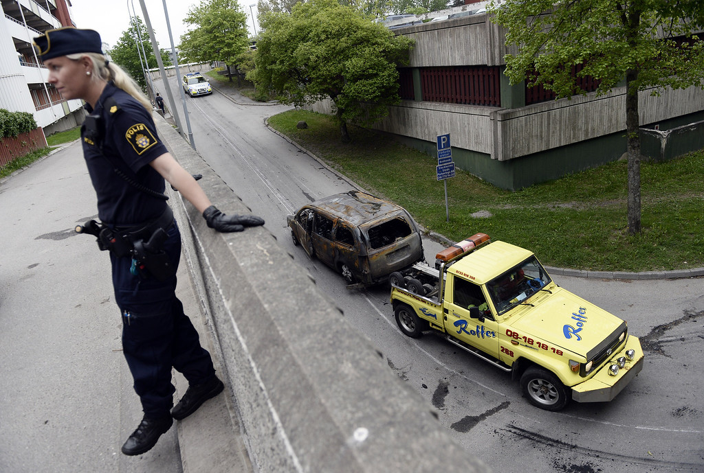 Description of . A Police officer stands guard as a  burned-out van is towed away after youths rioted in Husby, northern Stockholm on May 21, 2013. Youths in the immigrant-heavy Stockholm suburb of Husby torched cars and threw rocks at police, in riots believed to be linked to the deadly police shooting of a local resident. An apartment building had to be evacuated for an hour during the night after fire spread inside a garage, and shops and schools in the low-income neighbourhood had their windows crashed. JONATHAN NACKSTRAND/AFP/Getty Images