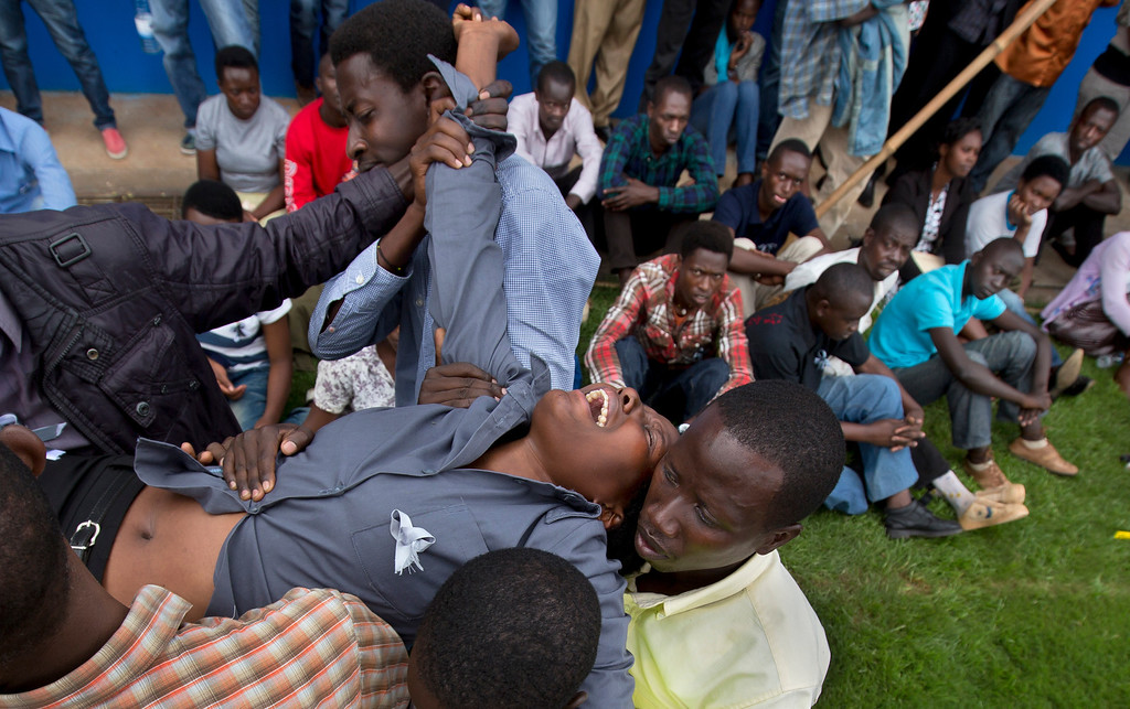 Description of . A wailing and distraught Rwandan woman, one of dozens overcome by grief at recalling the horror of the genocide, is carried away to receive help during a public ceremony to mark the 20th anniversary of the Rwandan genocide, at Amahoro stadium in Kigali, Rwanda Monday, April 7, 2014.  (AP Photo/Ben Curtis)