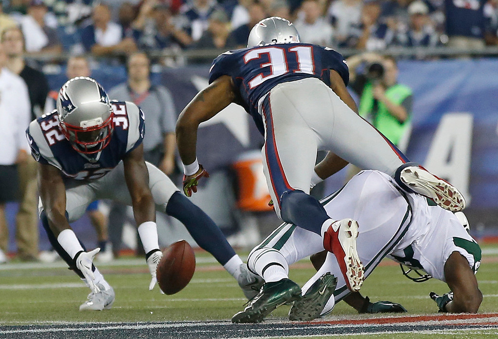 Description of . New England Patriots free safety Devin McCourty (32) scoops up a fumble by New York Jets wide receiver Stephen Hill, right, after he was knocked to the ground by Patriots cornerback Aqib Talib (31) in the first quarter of an NFL football game Thursday, Sept. 12, 2013, in Foxborough, Mass. (AP Photo/Elise Amendola)