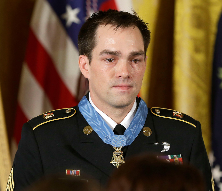Description of . Medal of Honor recipient, retired Staff Sgt. Clinton Romesha is seen on stage during the ceremony in the East Room of the White House in Washington, Monday, Feb. 11, 2013, where President Barack Obama bestowed the medal. (AP Photo/Pablo Martinez Monsivais)