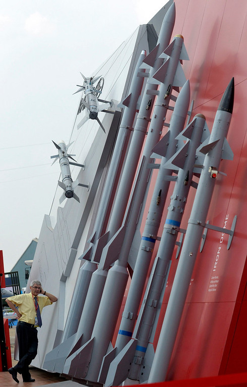 Description of . An official makes a phone call on his mobile phone while standing next to Rafael's missiles on display at the
