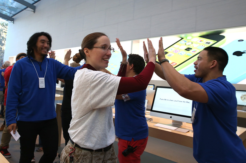 Description of . Apple Store employees greet customers who are purchasing the new iPhone on September 20, 2013 in Palo Alto, California.   (Photo by Justin Sullivan/Getty Images)