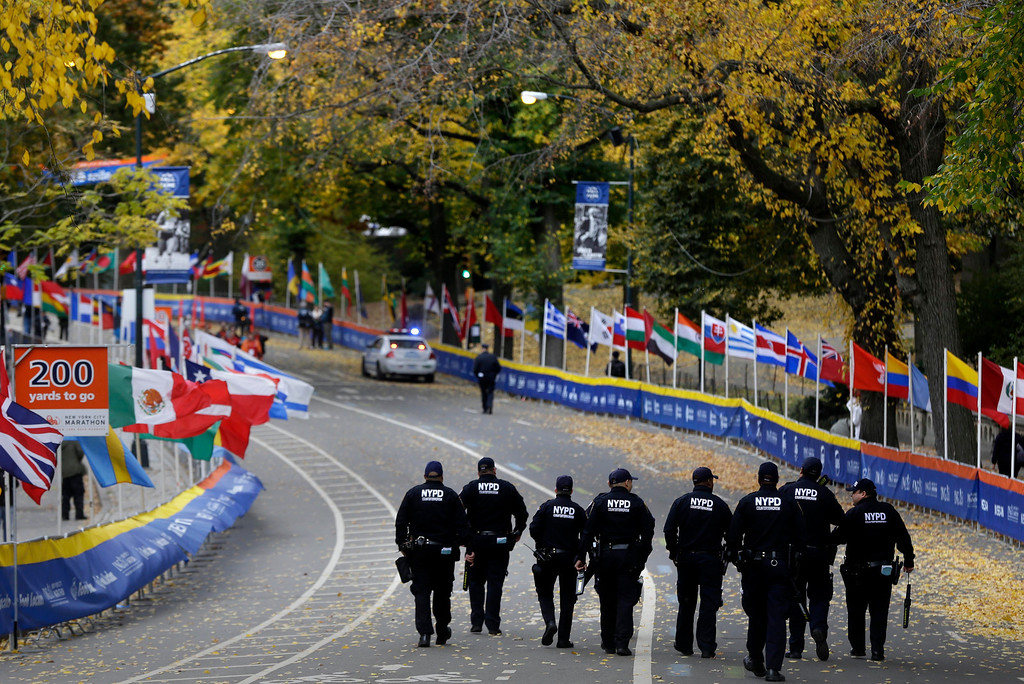 Description of . Counter-terrorism police officers walk the course near the finish line of the 2013 New York City Marathon in New York, Sunday, Nov. 3, 2013. The increased security at the marathon will be most evident near the finish line in Central Park. There will be barricades around the park to limit entry points, bag checks and bomb-sniffing dogs. (AP Photo/Seth Wenig)