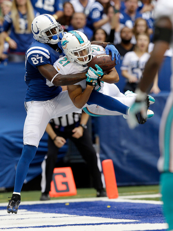 Description of . Miami Dolphins' Brent Grimes (21) intercepts a pass in the end zone intended for Indianapolis Colts' Reggie Wayne (87) during the second half an NFL football game Sunday, Sept. 15, 2013, in Indianapolis. (AP Photo/Michael Conroy)