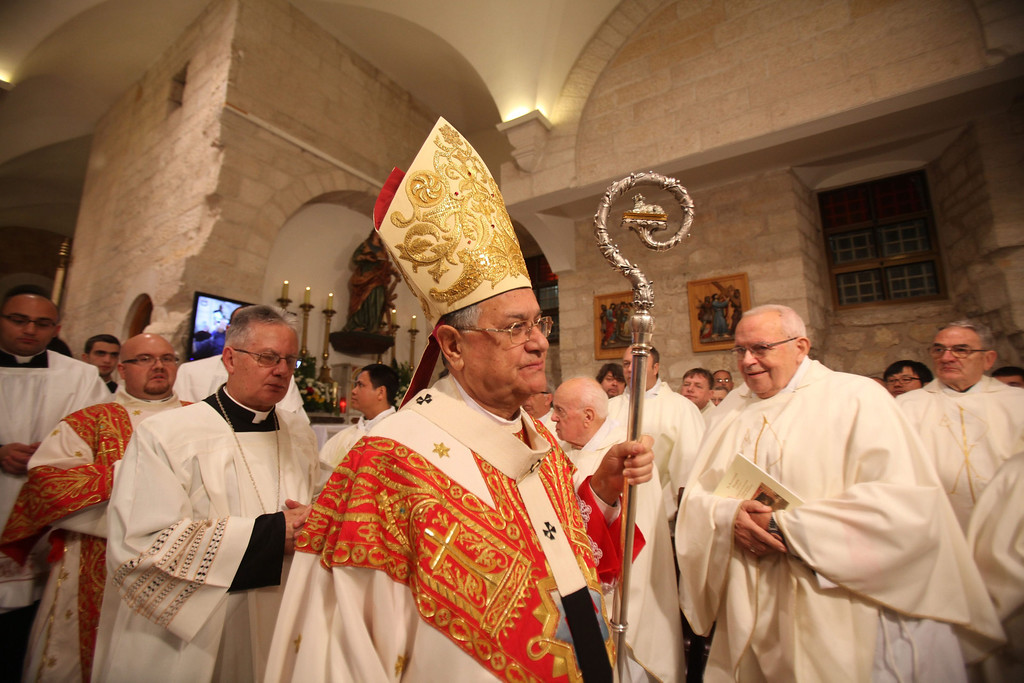 Description of . Foud Twal (C), archbishop of the Roman Catholic Church and serving as Latin Patriarch of Jerusalem, leads a Christmas Eve Midnight Mass at the Church of the Nativity, in Bethlehem, West Bank, 25 December 2013. Thousands of pilgrims made their way to the Church of the Nativity this week to worship at the sacred site believed to be the birthplace of Jesus. Palestinian president Mahmoud Abbas attended the mass.  EPA/MUSA AL-SHAER/POOL