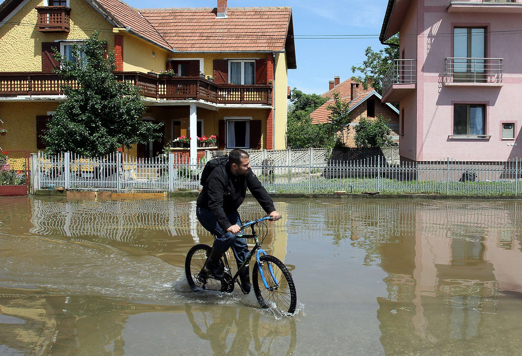 Description of . A man rides a bicycle through flooded streets  of Svilajnac, 120 kilometers south of Belgrade, on May 20, 2014. The Balkans were on alert Tuesday as swollen rivers were due to reach new peaks after days of devastating floods and landslides that have claimed at least 49 lives.  AFP PHOTO / SASA DJORDJEVIC/AFP/Getty Images