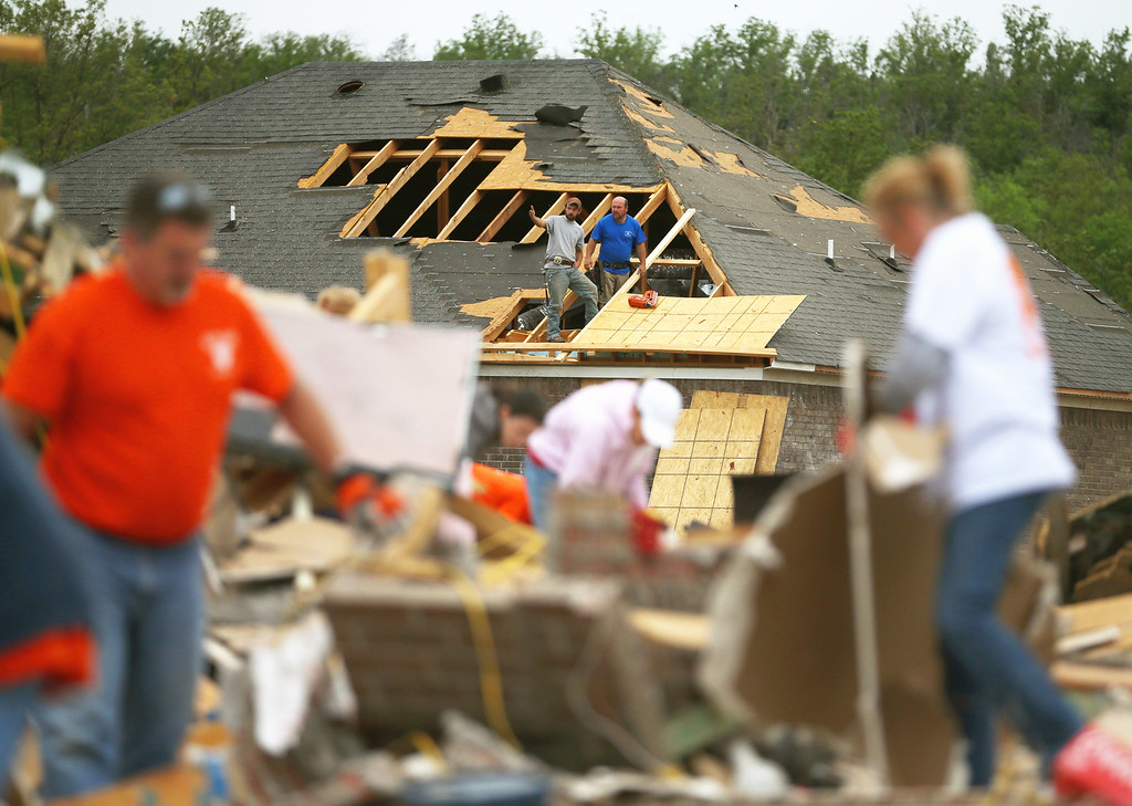 Description of . Volunteers help clean debris at the site of a home that was detroyed after a tornado hit the area April 29, 2014 in Vilonia, Arkansas. Deadly tornadoes ripped through the region April 27, leaving more than a dozen dead.  (Photo by Mark Wilson/Getty Images)