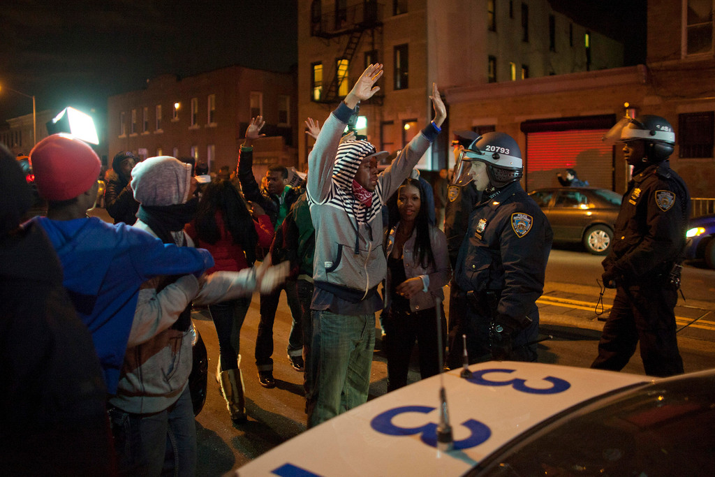 Description of . People confront New York Police Department (NYPD) officers during a protest against the killing of 16-year-old Kimani