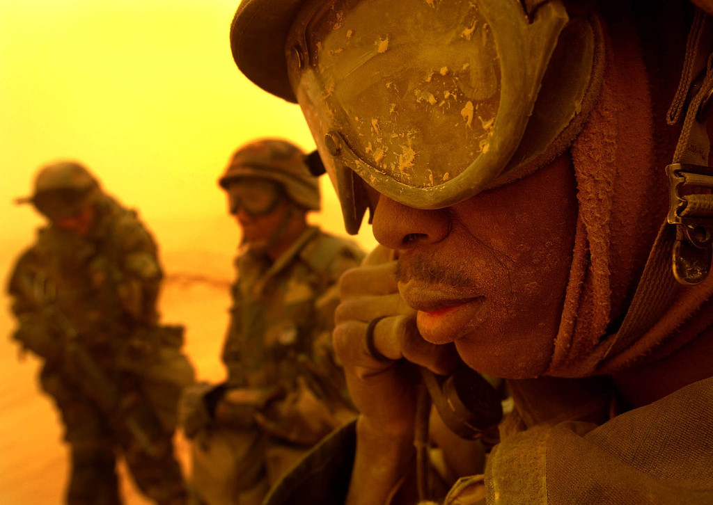 . A US Army combat engineer tries to get a radio connection at a checkpoint between the cities of Najaf and Karbala as another sandstorm turns the daylight orange on March 26, 2003. REUTERS/Kai Pfaffenbach
