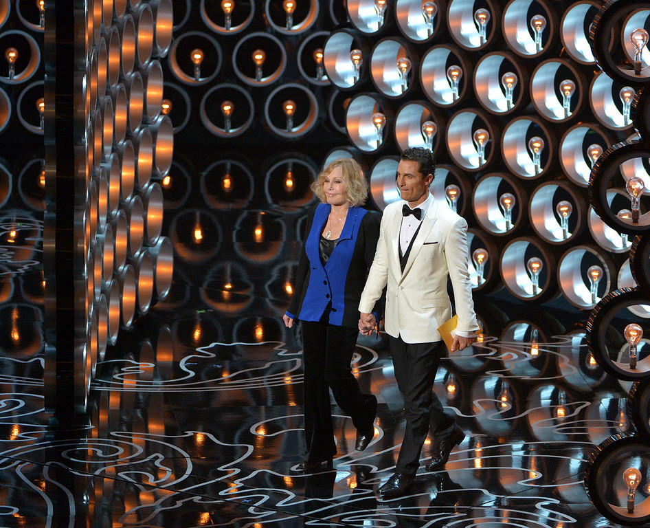 Description of . Kim Novak, left, and Matthew McConaughey walk on stage during the Oscars at the Dolby Theatre on Sunday, March 2, 2014, in Los Angeles.  (Photo by John Shearer/Invision/AP)