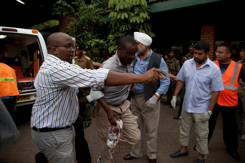 Description of . An injured person is helped on his arrival at the Aga Khan Hospital in Nairobi after an attack at the Westgate Mall, an upscale shopping mall in Nairobi, Kenya Saturday Sept. 21, 2013, where shooting erupted when armed men staged an attack. (AP Photo/Jason Straziuso)