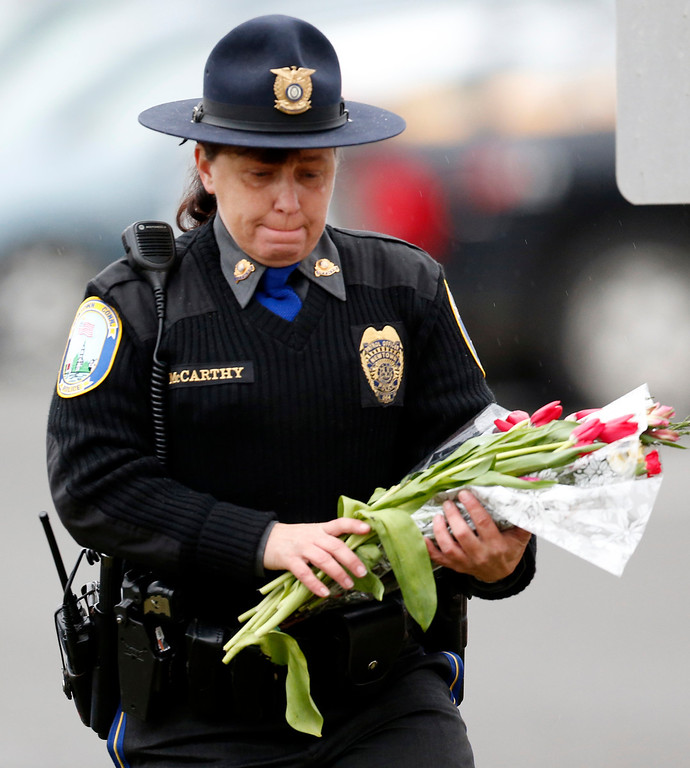 Description of . Newtown Police Officer Maryhelen McCarthy places flowers at a makeshift memorial outside St. Rose of Lima Roman Catholic Church, Sunday, Dec. 16, 2012, in Newtown, Conn. On Friday, a gunman allegedly killed his mother at their home and then opened fire inside the Sandy Hook Elementary School, killing 26 people, including 20 children. (AP Photo/Julio Cortez)