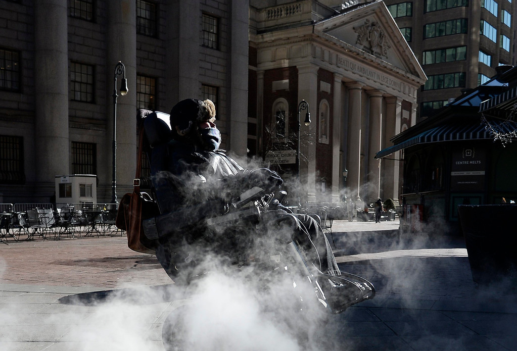 Description of . A woman in wheelchair passes a steam grate in Lower Manhattan Borough of New York, New York, USA, 07 January 2013. Many parts of the United States are experiencing record cold temperatures due to an usual polar vortex of arctic air.  EPA/ANDREW GOMBERT