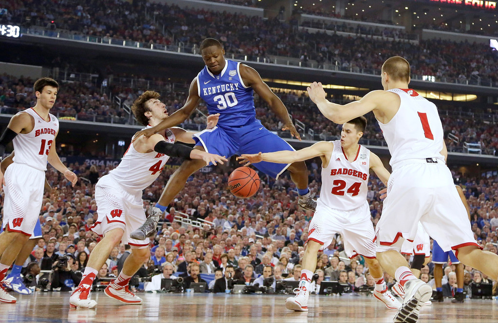 Description of . Kentucky forward Julius Randle (30) loses the ball as Wisconsin forward Frank Kaminsky (44), guard Bronson Koenig (24) and Ben Brust (1) defend during the first half of the NCAA Final Four tournament college basketball semifinal game Saturday, April 5, 2014, in Arlington, Texas. (AP Photo/Eric Gay)