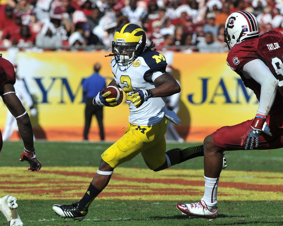 Description of . Running back Vincent Smith #2 of the Michigan Wolverines rushes upfield against the South Carolina Gamecocks in the Outback Bowl January 1, 2013 at Raymond James Stadium in Tampa, Florida.  (Photo by Al Messerschmidt/Getty Images)