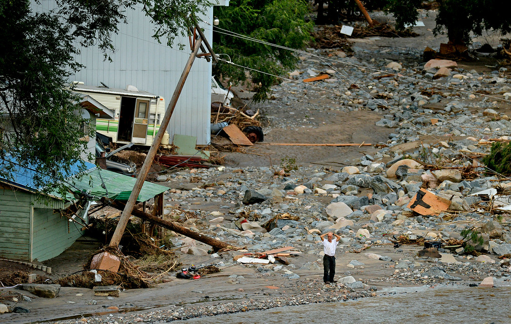 Description of . Standing amid an enormous debris field near the mouth of Big Thompson Canyon, a man holds his head while watching the river. A stretch of 20 miles of U.S. 34 between Loveland and Estes Park was severely damaged by flooding.