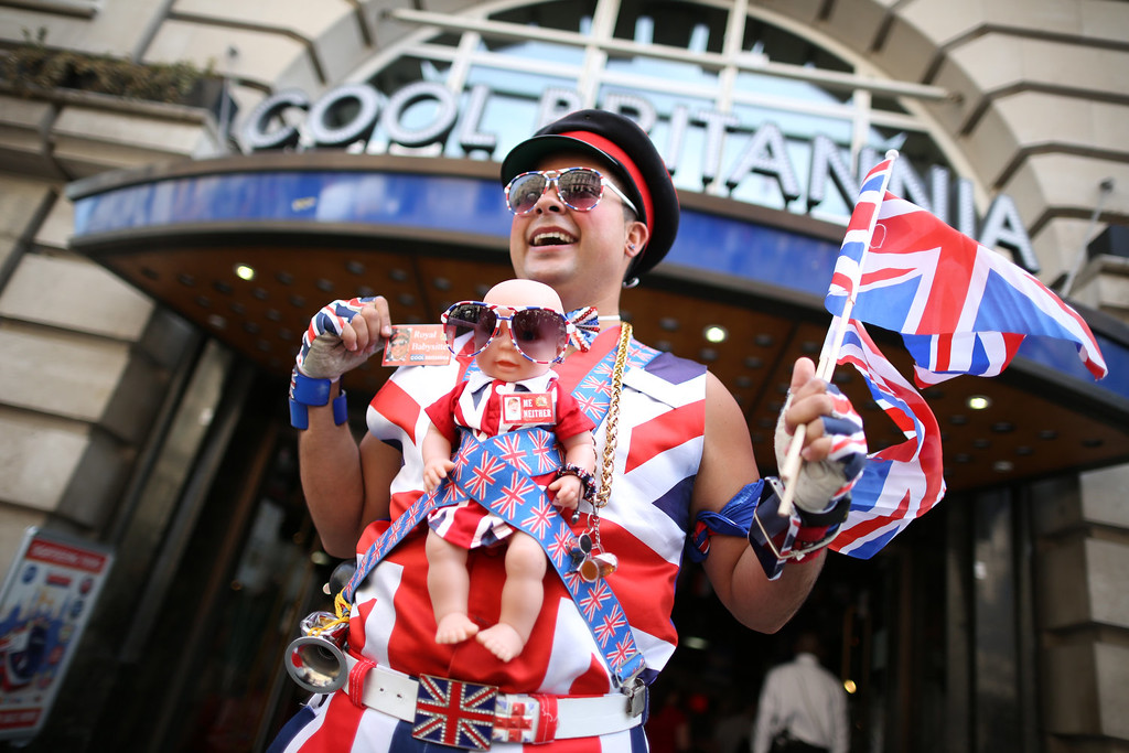 Description of . Promotions manager Daniel Obando wears a baby doll wrapped in union flag decorations as he stands in Piccadilly as the UK prepares for the birth of the first child of the Duke and Duchess of Cambridge on July 12, 2013 in London, England.  (Photo by Peter Macdiarmid/Getty Images)