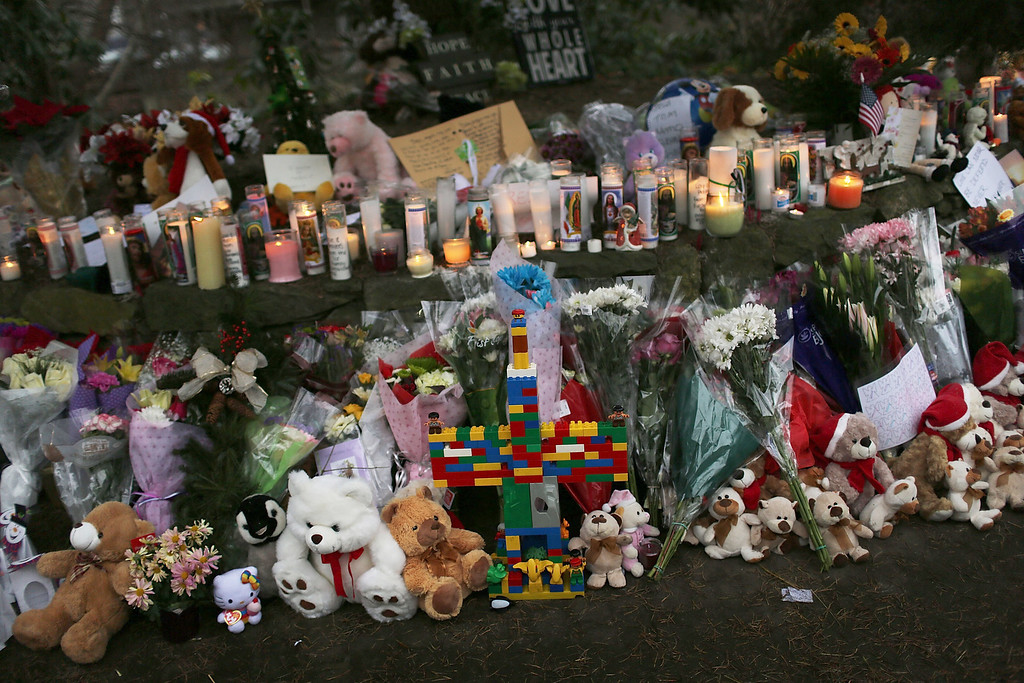 Description of . NEWTOWN, CT - DECEMBER 16:  Teddy bears, flowers and candles in memory of those killed, are left at a memorial down the street from the Sandy Hook School December 16, 2012 in Newtown, Connecticut. Twenty-six people were shot dead, including twenty children, after a gunman identified as Adam Lanza opened fire at Sandy Hook Elementary School. Lanza also reportedly had committed suicide at the scene. A 28th person, believed to be Nancy Lanza, found dead in a house in town, was also believed to have been shot by Adam Lanza.  (Photo by Spencer Platt/Getty Images)