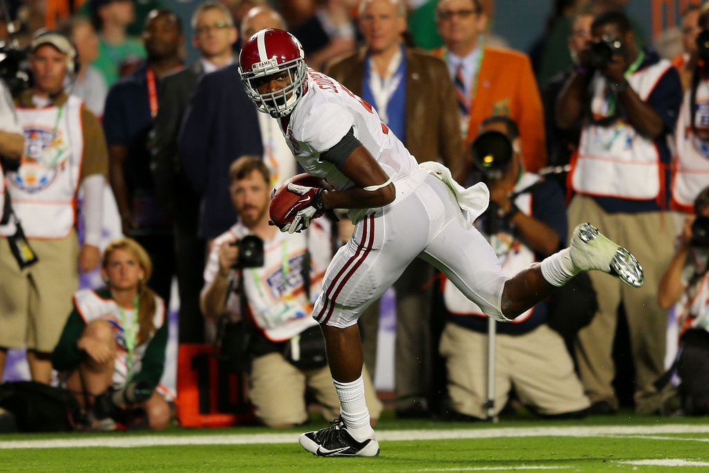 Description of . MIAMI GARDENS, FL - JANUARY 07:  Amari Cooper #9 of the Alabama Crimson Tide runs with ball on his way to scoring a touchdown in the third quarter against the Notre Dame Fighting Irish during the 2013 Discover BCS National Championship game at Sun Life Stadium on January 7, 2013 in Miami Gardens, Florida.  (Photo by Mike Ehrmann/Getty Images)
