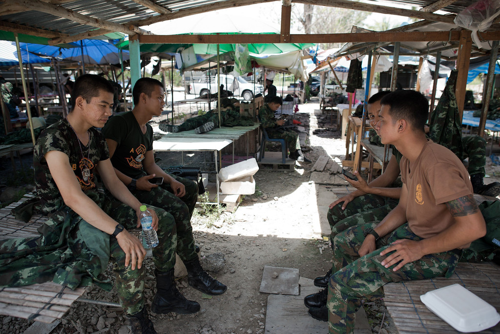 Description of . Thai army soldiers take a break from checkpoint near where pro-government ''Red shirts'' have been rallying for days on the outskirts of Bangkok on May 20, 2014. AFP PHOTO/ Nicolas ASFOURI/AFP/Getty Images