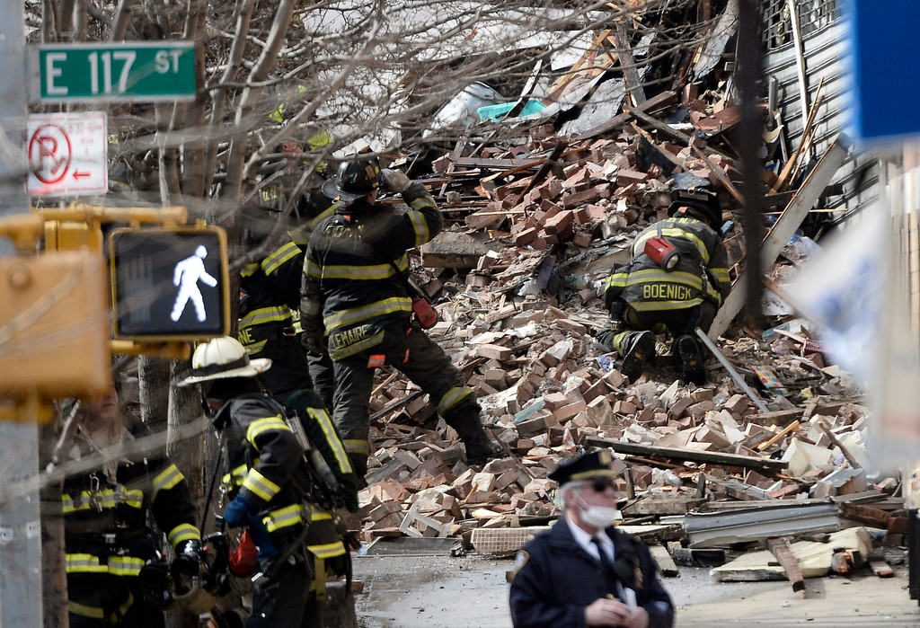 Description of . Firefighters and a police officer on the scene where a group of buildings were damaged by fire and a possible explosion in New York, New York, USA, 12 March 2014. EPA/ANDREW GOMBERT