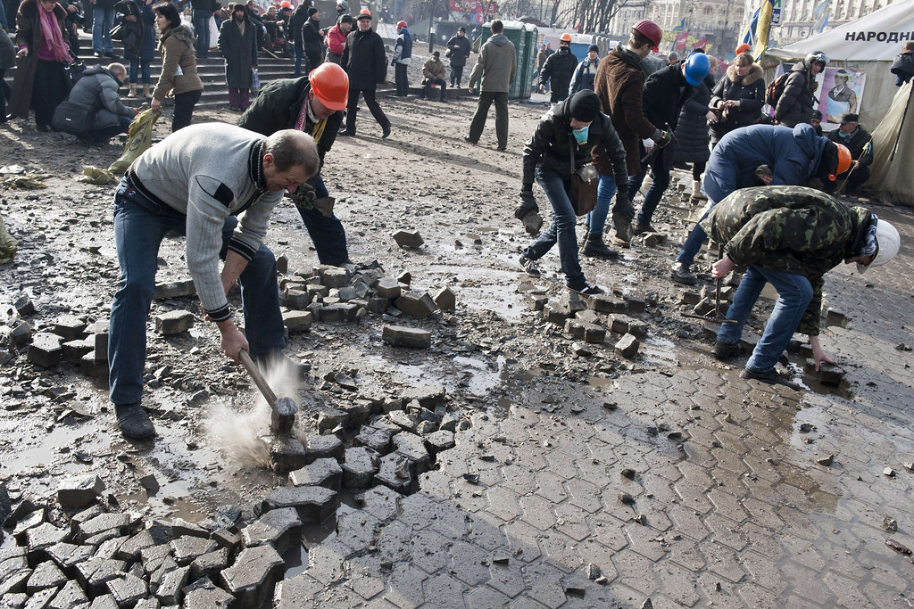 Description of . Anti-government protesters dig up cobblestones to use them as rocks against riot police on Kiev's Independence square on February 19, 2014.  AFP PHOTO / PIERO  QUARANTA/AFP/Getty Images