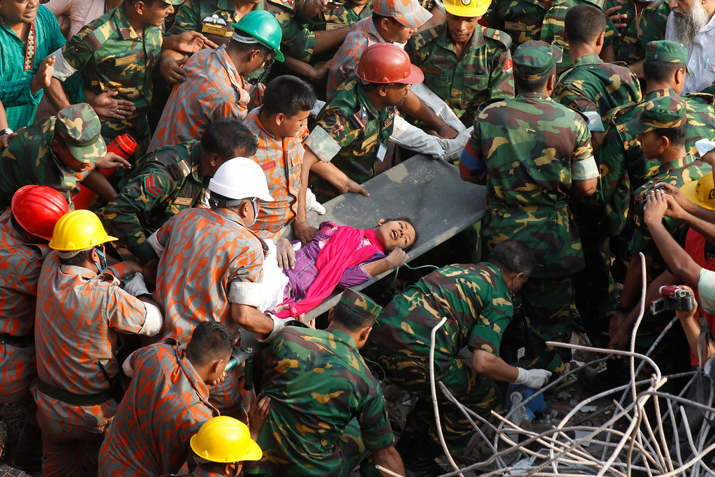 Description of . Bangladeshi rescuers retrieve garment worker Reshma from the rubble of a collapsed building in Savar on May 10, 2013, seventeen days after the eight-story building collapsed. AFP PHOTO/STRSTRDEL/AFP/Getty Images