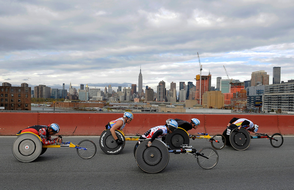 Description of . The mens wheelchair competitors cross the Pulaski bridge into the Queens borough of New York during the New York City Marathon on Sunday, Nov. 3, 2013. Marcel Hug, of Switzerland, finished first and Ernst Van Dyk, of South Africa, finished second. (AP Photo/Kathy Kmonicek)