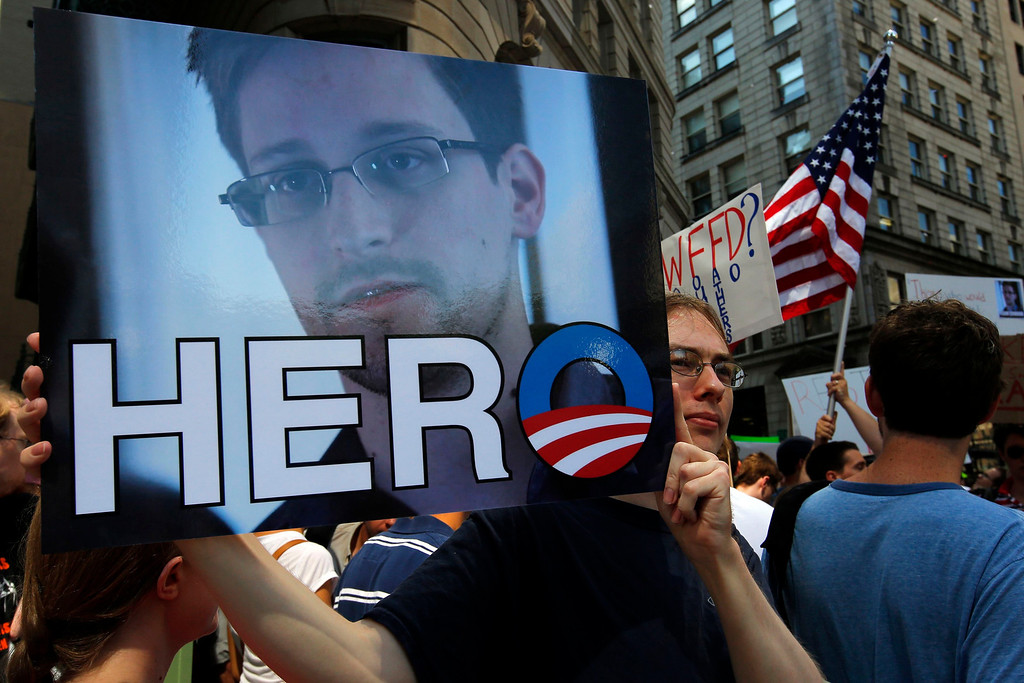 Description of . A demonstrator holds a sign with a photograph of former U.S. spy agency NSA contractor Edward Snowden and the word