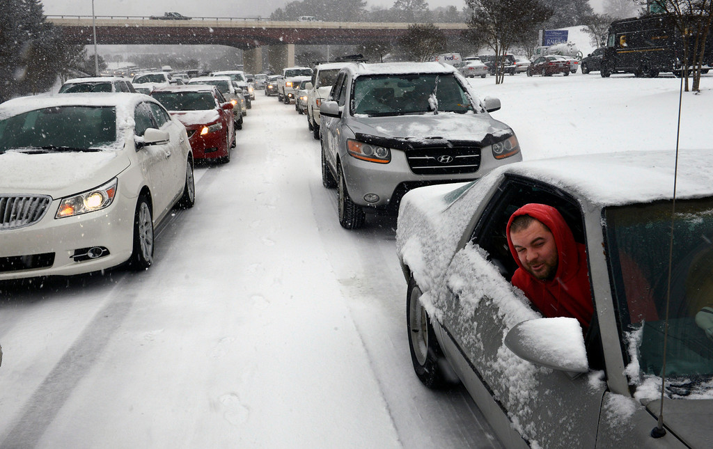 Description of . Kevin Miller looks out of the passenger window of his friend\'s car as they sit in stuck traffic during a winter storm Wednesday Feb. 12, 2014, in Raleigh, N.C. (AP Photo/The News & Observer, Scott Sharpe)