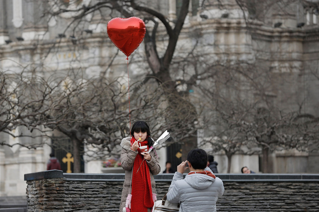 Description of . A woman holding a heart balloon poses for a photo during on Valentine's Day February 14, 2013 in Beijing, China. Young Chinese couples have embraced the Western concept of Valentine's Day with hawkers selling roses and chocolates.  (Photo by Lintao Zhang/Getty Images)