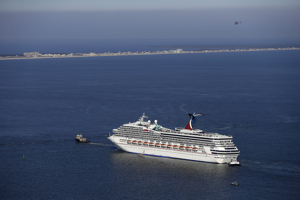 Description of . The disabled Carnival Lines cruise ship Triumph is towed to harbor off Mobile Bay, Ala., Thursday, Feb. 14, 2013.  (AP Photo/Gerald Herbert)