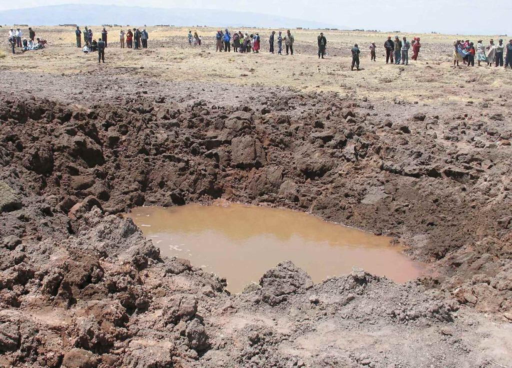 Description of . In this photo released by La Republica Newspaper, people watch a crater in Puno, Peru, Sunday, Sept. 16, 2007, caused by a supposed meteorite that crashed in southern Peru over the weekend causing hundreds of people to suffer headaches, nausea and respiratory problems, a health official said Tuesday, Sept. 18, 2007. (AP Photo/ La Republica Newspaper)