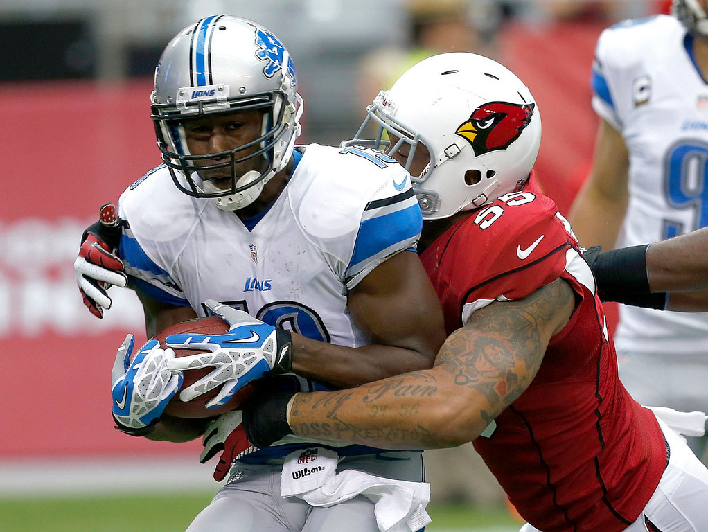 Description of . Detroit Lions wide receiver Nate Burleson is tackled by Arizona Cardinals defensive end John Abraham (55) during the first half of a NFL football game, Sunday, Sept. 15, 2013, in Glendale, Ariz. (AP Photo/Ross D. Franklin)